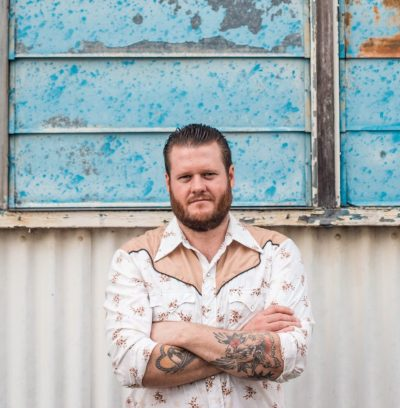 A broadset man with a short beard and tattoos on his forearms stands in front of corrugated white metal and blue peeling windows